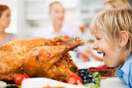 Surprised boy looking at stuffed thanksgiving turkey.